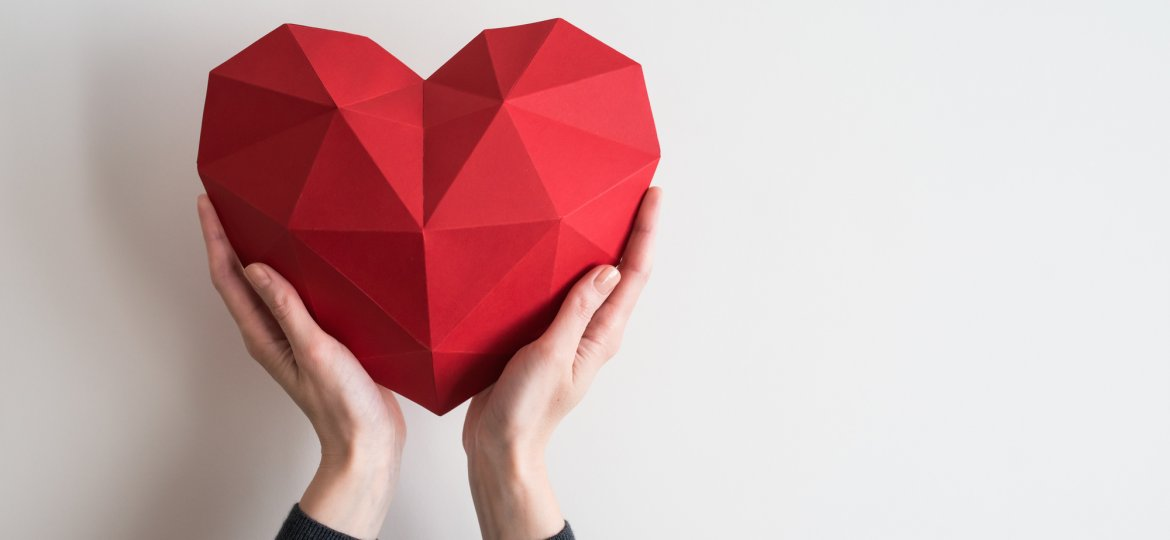Female hands holding red polygonal heart shape